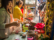 07 MARCH 2014 - MAE SOT, TAK, THAILAND: A betel vendor (left) sells betel to a woman in the Burmese market in Mae Sot. Betel is still widely chewed in Myanmar (Burma) but public health campaigns have reduced the number of Thais who chew the mild narcotic. Among Thais it's mostly older people who still chew betel.        PHOTO BY JACK KURTZ