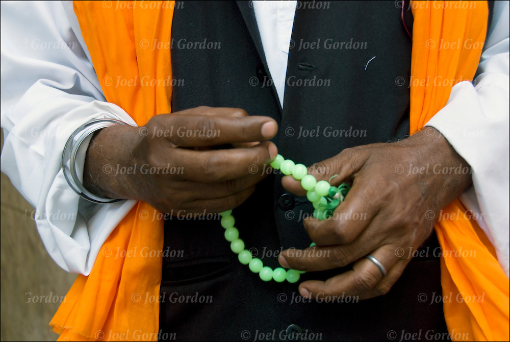 Close up of portrait of Sikh hands holding prayer beads praying..