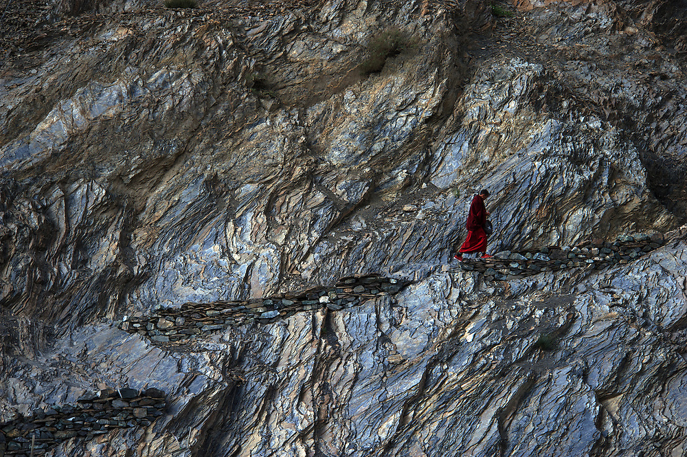 A lone monk climbs to his residential quarters. Monks and pilgrims mix to celebrate the Lamayuru Festival 5-6 June, 2013, Lamayuru Monastery. Lamayuru Gompa (monastery) is built above the ruins of the old one, along the Srinagar-Leh highway.