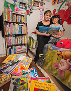 Amanda Cruz poses for a photograph while reading with her daughter Jazlyn at their home, January 19, 2017.