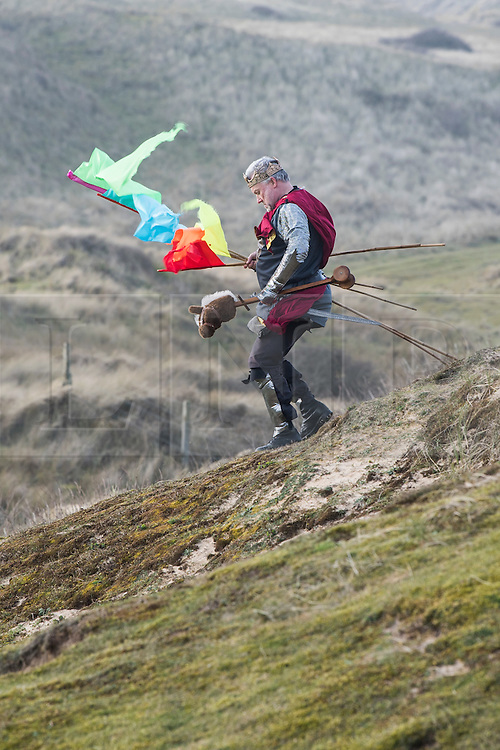 © Licensed to London News Pictures. 05/03/2017. PERRANPORTH, CORNWALL, UK.  The King descending the dunes. St. Piran's Day in Cornwall. St Piran is the patron Saint of Sinners in Cornwall and it is his flag that is recognised as the Cornish flag. Today his arrival from Ireland to Cornwall is celebrated across Cornwall especially in Perranporth where it is believed that he landed. He set up an Oratory and a Church the remains of which have been recently uncovered in the sand dunes at Perranporth..  Photo credit: MARK HEMSWORTH/LNP