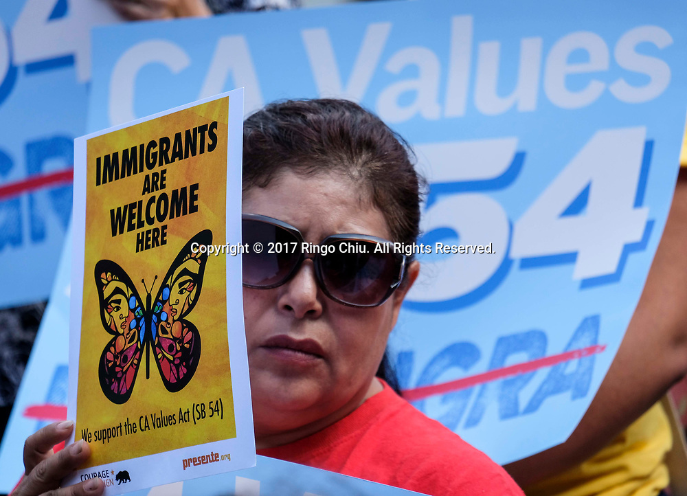 A woman holding sign protests in Los Angeles, the United States, on September 14, 2017, to call on the state Assembly to pass SB 54, the so-called sanctuary state legislation. The bill would protect communities from President Donald Trump's ``mass deportation agenda'' and prevent state resources being used to separate families. &quot;My grandparent came here freely, that's what this country should be about.&quot; A protester, Sam Samalin said,  (Xinhua/Zhao Hanrong)(Photo by Ringo Chiu)<br /> <br /> Usage Notes: This content is intended for editorial use only. For other uses, additional clearances may be required.