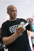 Democratic presidential hopeful Senator Cory Booker hands out pieces of birthday cake after blowing out the candles during a visit to Fresh Future Farm April 27, 2019 in North Charleston, South Carolina. Booker spent his 50th birthday helping out at the urban farm as part of his Justice For All tour.