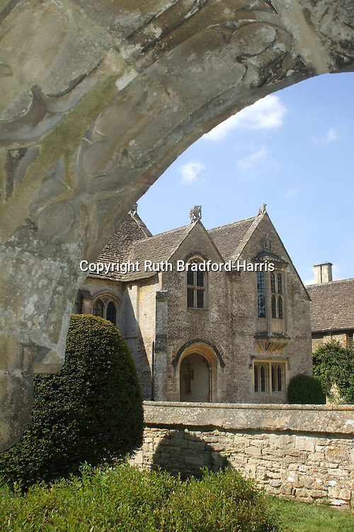 The idyllic 15th century Great Chalfield Manor seen through the Gothic arched doorway of the parish church.<br /> <br /> Date taken: 03 May 2011.