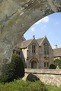 The idyllic 15th century Great Chalfield Manor seen through the Gothic arched doorway of the parish church.<br />