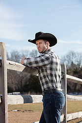 All American Cowboy leaning on a wooden fence