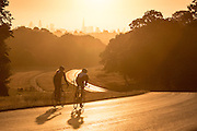 UNITED KINGDOM, London: 04 August 2015 A pair of cyclists take a ride through Richmond Park this morning in front of the London landscape and a rising sun . Rick Findler / Story Picture Agency