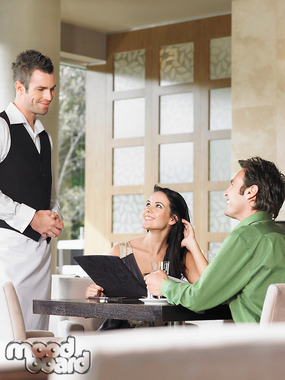 Couple ordering from waiter at outdoor restaurant
