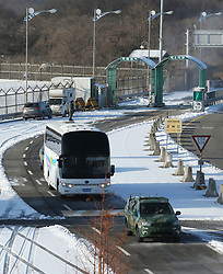 25 January 2018 - Paju, South Korea : (In this handout photos provided by Korea Pool) A bus carries a North Korean delegation past the customs, immigration and quarantine office near the border village of Panmunjom, in Paju, South Korea on January 25, 2018. Twelve North Korean female hockey players crossed the border into South Korea to form the rivals' first-ever Olympic team during next month's 2018 Pyeongchang Winter Olympic Games. Photo Credit: Korea Pool