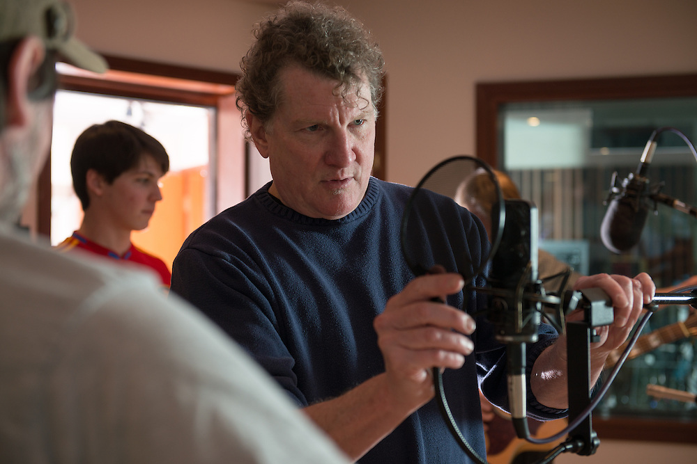 Eddie Ashworth adjusts the position of a microphone for musician Charles Stanton in between tracks during a recording session at MDIA Sound.