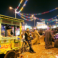 A man sells popcorn from a cart during a moulid in Tanta, Egypt. Every year following the October cotton harvest the Tanta moulid, a religious festival, is held to celebrate the memory of Ahmed al-Bedawi, a local 13th Century Sufi saint. The Tanta moulid, is the largest one held in Egypt attracting at least tens of thousands of people from around the country. October 2008.