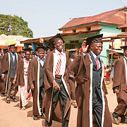 CAPTION: Timothy Leadership Training (TLT) graduands walk proudly down the main street of the town of Kaberamaido, on their way to their graduation ceremony. The training TLT provides helps many rural pastors, who have not had formal theological training, develop the skills they need to provide leadership to their congregations and families. LOCATION: Kaberamaido, Kaberamaido District, Uganda. INDIVIDUAL(S) PHOTOGRAPHED: TLT graduands.