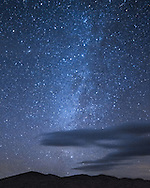 The northern milky way shines bright above the Kelso Sand Dunes in the Mojave National Preserve. At the top left is the Andromeda Galaxy. Clouds were moving across the sky quickly on this windy night.<br />