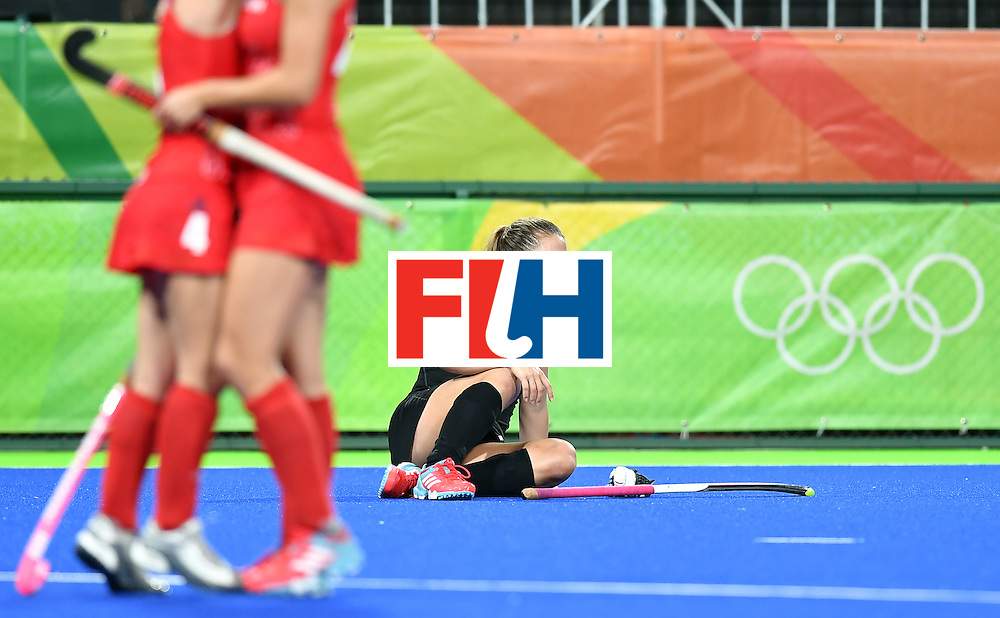 TOPSHOT - New Zealand's Rose Keddell (R) sits on the pitch as Britain's players celebrate their victory at the end of the women's semifinal field hockey New Zealand vs Britain match of the Rio 2016 Olympics Games at the Olympic Hockey Centre in Rio de Janeiro on August 17, 2016. / AFP / MANAN VATSYAYANA        (Photo credit should read MANAN VATSYAYANA/AFP/Getty Images)