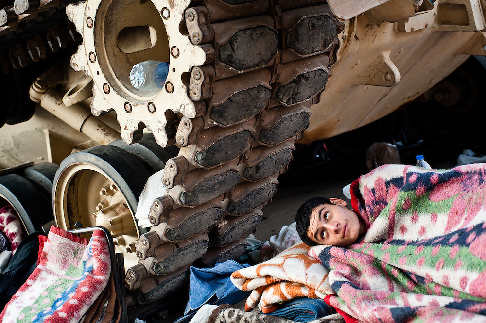 A boy rests under the treads of an Egyptian army tank in Tahrir Square, in downtown Cairo, where protesters have gathered since January 25, 2011, calling for the ouster of President Hosni Mubarak and his regime.