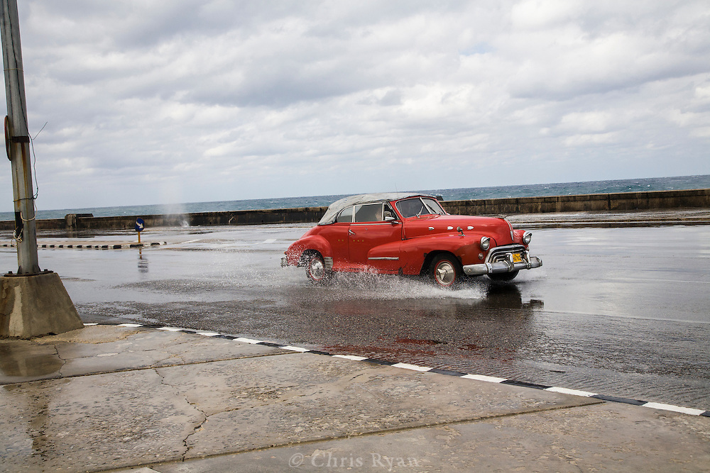 Classic car driving through flooded streets of the malecon, Havana, Cuba