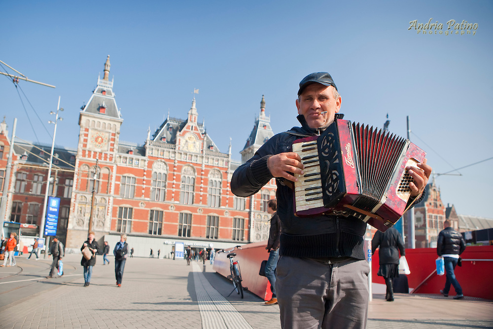 Performs for the camera in front of the Amsterdam Centraal Station