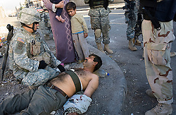 Members of the 1st Infantry, 17th Regiment, are seen aiding a wounded man, while helping Iraqi forces patrol in western Mosul, Iraq, Dec. 11, 2005. This is part of an effort to provide security in preparation for Iraq's first post-Saddam parliamentary elections. The western sector is home to Mosul's primarily Sunni population, which has been resistant to the American presence in Iraq.