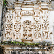Ornate religious decorations on the exterior of the monastery and church of Santa Clara (Saint Clair) in Antigua, Guatemala. The original foundation dates back to 1700 and the church was consecrated in 1715. It was run by nuns from the Second Franciscan Order of Poor Sisters of Saint Clair. In 1717 the earthquake of San Miguel caused extensive damages to the building. The church is now in ruins and is no longer a functional church.