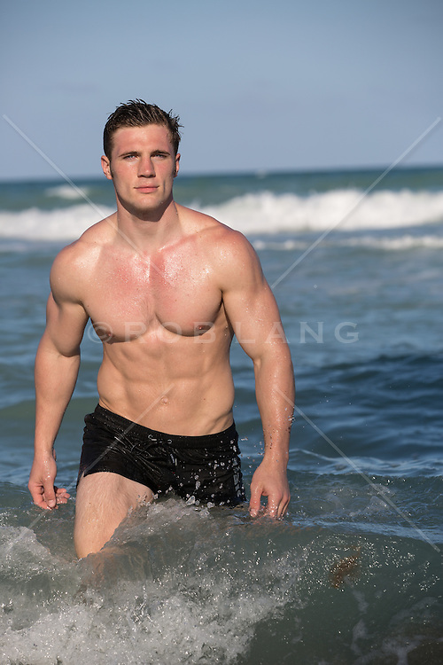 shirtless muscular man with a smooth body at the beach