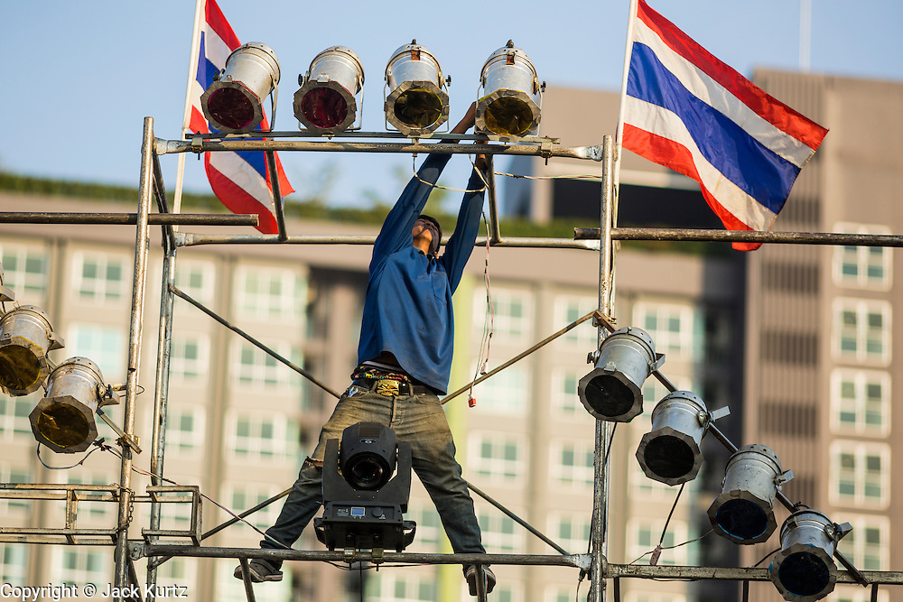 19 JANUARY 2014 - BANGKOK, THAILAND:  A member of the crew rigs the spotlights for a mor lam show in Khlong Tan Market in Bangkok. Mor Lam is a traditional Lao form of song in Laos and Isan (northeast Thailand). It is sometimes compared to American country music, song usually revolve around unrequited love, mor lam and the complexities of rural life. Mor Lam shows are an important part of festivals and fairs in rural Thailand. Mor lam has become very popular in Isan migrant communities in Bangkok. Once performed by bands and singers, live performances are now spectacles, involving several singers, a dance troupe and comedians. The dancers (or hang khreuang) in particular often wear fancy costumes, and singers go through several costume changes in the course of a performance. Prathom Bunteung Silp is one of the best known Mor Lam troupes in Thailand with more than 250 performers and a total crew of almost 300 people. The troupe has been performing for more 55 years. It forms every August and performs through June then breaks for the rainy season.              PHOTO BY JACK KURTZ