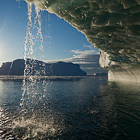 Greenland, Ilulissat, Setting midnight sun lights melting icebergs from Jakobshavn Isfjord along Disko Bay on summer evening