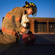 Camden-Wyoming Fire fighter Michelle Small rolls up a hose after hose removal training session Wednesday, July 6, 2011, in Camden-Wyoming Delaware.