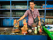 04 JANUARY 2016 - BANGKOK, THAILAND:       A vendor in Bang Chak Market takes down the Buddhist statues he had in his small shop the day the market closed for good. The market closed January 4, 2016. The Bang Chak Market serves the community around Sois 91-97 on Sukhumvit Road in the Bangkok suburbs. About half of the market has been torn down. Bangkok city authorities put up notices in late November that the market would be closed by January 1, 2016 and redevelopment would start shortly after that. Market vendors said condominiums are being built on the land.   PHOTO BY JACK KURTZ