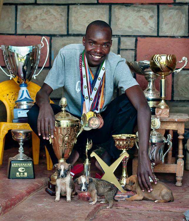 Iten Marathon champions photographed at their homes with their trophies: James Kwalia..Iten, is a small Kenyan town that has produced more world champion runners than any other place on Earth..The combination of high altitude, extreme motivation (winning a European marathon will earn a runner more money than his family could be making in a lifetime), and very hard work - most runners in Iten run around 20km per day, year round...
