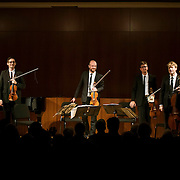 "February 22, 2015 - New York, NY : From left, The Calder Quartet's Ben Jacobson (violin), Andrew Bulbrook (violin), Jonathan Moerschel (viola), and Eric Byers (cello) take a bow after performing at the Brooklyn Public Library, Central Library as part of Carnegie Hall's ""Neighborhood Concert"" series on Sunday afternoon. CREDIT: Karsten Moran for The New York Times"