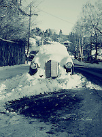 Old fashioned car buried under snow