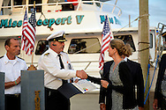 Freeport, NY, USA. Sept.10, 2014. LAURA CURRAN, Nassau County Legislator (D-Baldwin), shakes hands with Captain FRANK RIZZO and hands him a Citation honoring him, at a dockside remembrance ceremony in honor of victims of the terrorist attacks of September 11 2001, at the boat Miss Freeport V, on Freeport's Nautical Mile. Further ceremonies were held on board the vessel, which Capt. Rizzo, a host of the event, sailed from the Woodcleft Canal on the South Shore of Long Island, on the eve of the 13th Anniversary of the 9/11 attacks.