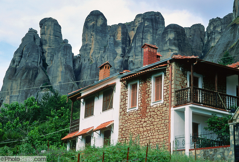 """Fantastic rock spires of Meteora rise above a house in Kastraki, near Kalambaka, in central Greece, Europe. Meteora (which means """"suspended in the air"""") is a complex of six Eastern Orthodox Christian monasteries built by medieval monks on natural rock pillars near Kalambaka, in central Greece, Europe. The sandstone and conglomerate of Meteora were formed in the cone of a river delta estuary emerging into a sea about 60 million years ago, then later uplifted and eroded into pinnacles. The isolated monasteries of Meteora helped keep alive Greek Orthodox religious traditions and Hellenic culture during the turbulent Middle Ages and Ottoman Turk occupation of Greece (1453-1829). UNESCO honored Meteora as a World Heritage Site in 1988. Visit early in the morning and in the off season to avoid crowds."""