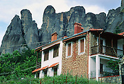 "Fantastic rock spires of Meteora rise above a house in Kastraki, near Kalambaka, in central Greece, Europe. Meteora (which means ""suspended in the air"") is a complex of six Eastern Orthodox Christian monasteries built by medieval monks on natural rock pillars near Kalambaka, in central Greece, Europe. The sandstone and conglomerate of Meteora were formed in the cone of a river delta estuary emerging into a sea about 60 million years ago, then later uplifted and eroded into pinnacles. The isolated monasteries of Meteora helped keep alive Greek Orthodox religious traditions and Hellenic culture during the turbulent Middle Ages and Ottoman Turk occupation of Greece (1453-1829). UNESCO honored Meteora as a World Heritage Site in 1988. Visit early in the morning and in the off season to avoid crowds."