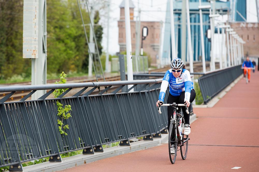 In Nijmegen fietst een vrouw op een racefiets over de Snelbinder, de fietsbrug die onderdeel is van het Rijn-Waalpad, de snelfietsroute tussen Arnhem en Nijmegen. Als de route helemaal klaar is, kunnen fietsers binnen 40 minuten van Arnhem naar Nijmegen fietsen. De snelfietsroute kent weinig obstakels en moet het aantrekkelijk maken om ook langere afstanden met de fiets af te leggen. <br /> <br /> A woman rides on a road bike at the Rijn-Waalpad, the fast cycling route between Arnhem and Nijmegen. When the route is finished, cyclists can get within 40 minutes from Arnhem to Nijmegen. The fast cycle route has few obstacles and to make it attractive to commute long distances by bicycle.