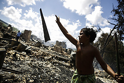 December 12, 2016 - Recife, Brazil - Williams Adriel, just 9 years old, works to help his family, who had all belongings burned. During the morning of Monday (12), the fire hit the favela Vila Santa Luzia, in the city of Recife. Dozens of people had their homes burned by fire and three men had severe burns on their bodies. In Recife, Northeast Brazil, December 12, 2016. (Credit Image: © Diego Herculano/NurPhoto via ZUMA Press)