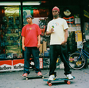 Two teenagers on their skateboards outside some shops, USA