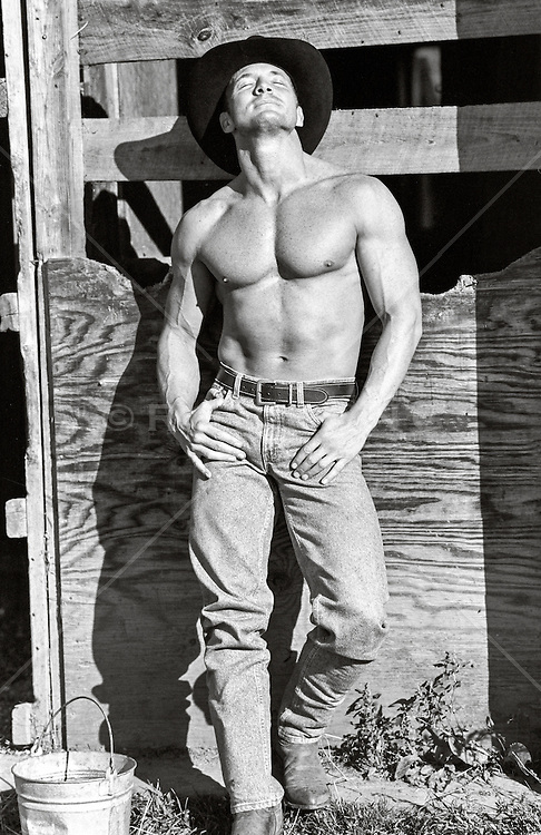 shirtless cowboy soaking up the sun while leaning against a barn door