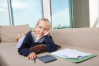 Portrait of little girl studying while lying on sofa