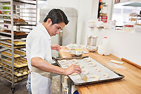Side view of a young male baker making dough in bakery