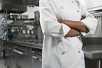 Female chef with arms crossed in kitchen mid section