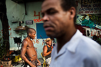 Residents hang out during a neighborhood party, in Complexo da Mare, Rio de Janeiro, Brazil, on Saturday, April 27, 2013. Complexo da Mare, is a complex of 16 communities, in the north zone of Rio de Janeiro. It is the largest complex of favelas with 130,000 residents. It is targeted for pacification as the city prepares for the 2014 World Cup and the 2016 Olympics. Four factions run the complex -  three drug gangs and the militia. The rival gangs fight for control of the drug trade. Although crime is low in the favelas by rule  of law enforced by the gangs, cross-fire shootings and gang violence is often high. Neighborhood associations are an integral part of community development within Mare, making up for a lack of government assistance.