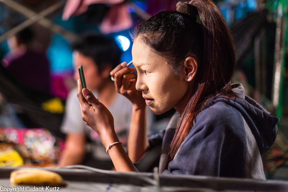 19 JANUARY 2014 - BANGKOK, THAILAND:  A performer in a mor lam show puts on makeup before going on stage at a mor lam show in Khlong Tan Market in Bangkok. Mor Lam is a traditional Lao form of song in Laos and Isan (northeast Thailand). It is sometimes compared to American country music, song usually revolve around unrequited love, mor lam and the complexities of rural life. Mor Lam shows are an important part of festivals and fairs in rural Thailand. Mor lam has become very popular in Isan migrant communities in Bangkok. Once performed by bands and singers, live performances are now spectacles, involving several singers, a dance troupe and comedians. The dancers (or hang khreuang) in particular often wear fancy costumes, and singers go through several costume changes in the course of a performance. Prathom Bunteung Silp is one of the best known Mor Lam troupes in Thailand with more than 250 performers and a total crew of almost 300 people. The troupe has been performing for more 55 years. It forms every August and performs through June then breaks for the rainy season.              PHOTO BY JACK KURTZ