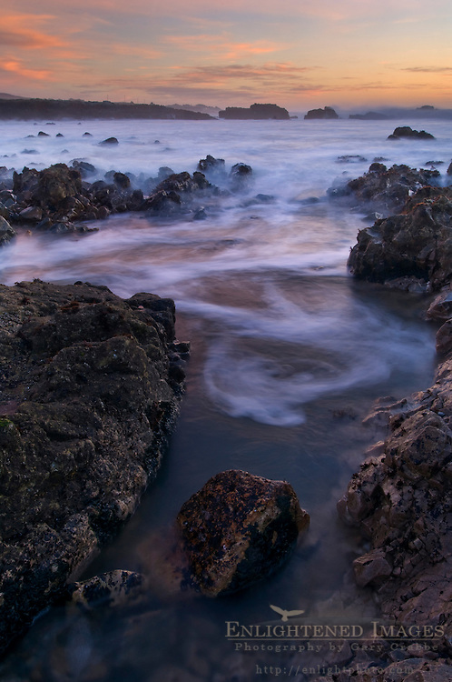 Waves moving through coastal rocks at low tide at sunset, Pescadero State Beach, San Mateo County coast, California