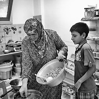 Egypt / Syrian refugees / Syrian refugee Moazez Masri, 50-years-old, originally from Homs prepares dinner for her family with her grandson Yehia Naguib, 12-years-old, in their rented apartment in Beit Al Alia neighborhood in the 6th of October City outside of Cairo, Egypt, Monday, May 27, 2013. Moazez's family left Homs 1 year and a half ago, stayed in Latakia for 9 months and has been displaced several times. 'We had to leave because the situation was very bad, raids, no water, no electricity, no food. We didn't have any choice but to go'.  / UNHCR / Shawn Baldwin / May 2013
