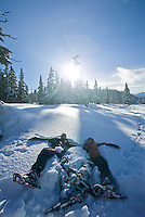 Two Snowshoer's, having fun, relax and take a break by lying down in the snow at Paradise Meadows, in Strathcona Park.  Mt. Washington, The Comox Valley, Vancouver Island, British Columbia, Canada.