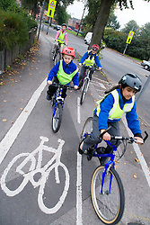 Group of children cycling home from school on a designated cycle path accompanied by a parent,