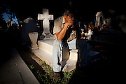 "Heraldo Menoez sits on a loved one's grave at a cemetery in the town of Zacapu, Michoacan, Mexico, on ""Noche de Muertos"" (Day of the Dead) on Nov. 2, 2011. The ritual has profound significance for the local people who celebrate deceased loved ones on the cheerful and solemn occasion. ..©Benjamin B Morris"