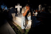 """Heraldo Menoez sits on a loved one's grave at a cemetery in the town of Zacapu, Michoacan, Mexico, on """"Noche de Muertos"""" (Day of the Dead) on Nov. 2, 2011. The ritual has profound significance for the local people who celebrate deceased loved ones on the cheerful and solemn occasion. ..©Benjamin B Morris"""