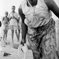 A spirit medium assistant to the treat healer Shakanda at dawn after an all night Morupa or drumming that is intended to cure people of spiritual afflictions and also often where Shakanda used his skills to heal a communities conflicts. 1985 / 1086  Chobe, Botswana. Photo Greg Marinovich